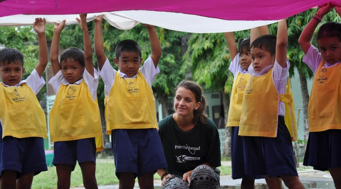 A volunteer working with children in Thailand crouches under a parachute during an activity with kids at her Childcare placement.
